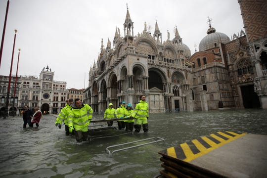 Municipality workers carry wooden boards to create a trestle bridge in a flooded St. Mark's Square at Venice, on Friday.The high-water mark hit 187 centimeters (74 inches) late Tuesday, meaning more than 85% of the city was flooded. The highest level ever recorded was 194 centimeters (76 inches) during infamous flooding in 1966.