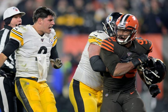 Cleveland Browns defensive end Myles Garrett is held back after striking Pittsburgh Steelers quarterback Mason Rudolph (2) in the head with his helmet.