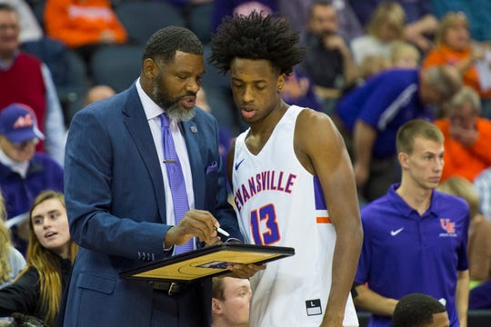 Evansville Head Coach Walter McCarty and Evansville's DeAndre Williams (13) go over a play before tipoff against the Indiana University Kokomo Cougars at Ford Center Thursday evening, Nov. 14, 2019.