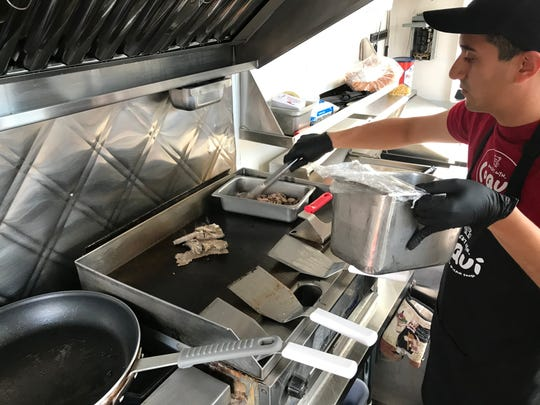 Sergio Torres cooks roasted pork for one of Rocky Mountain Coqui's pernil plates Friday morning in Fort Collins.