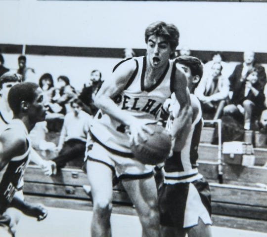 Dabo Swinney rebounds a basketball during a Pelham High School game in Alabama.