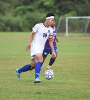 In this Nov. 15 file photo, Harvest Christian Academy's James Lee dribbles the ball against the Okkodo BUlldogs during an IIAAG Boys Soccer match at the Harvest Christian Academy Field. Lee was chosen as the Most Valuable Player of the Boys Soccer season.