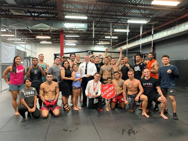 Members and staff of Steel Athletics Gym in Tamuning along with representatives of the Salvation Army gather for a check presentation Nov. 14 at the Tamuning gym. Glorified Sparring 5 raised $1,000 for the Salvation Army.