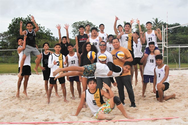 Led by the Levitating Libero VJ Rosario, members of the GW Geckos and Tiyan High Titans boys beach volleyball teams gather for their best aerial photo bomb of their coaches at center, from left, Kendra Byrd, Greg Esplana and Rod Pama. The players know the trio are volunteer coaches this season, and that makes them work extra hard at practice to make it all worth it.