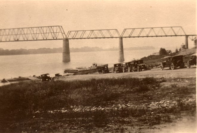 Autos stand parked on the drive that led down to the Ohio River at the riverfront in an early 1920s era photo marked by the pre-1932 railroad bridge. Note the ferry at center and dock at left, as well as the weeds growing before the riverfront was paved.