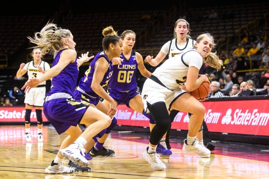 Iowa guard Kathleen Doyle (22) draws a foul from North Alabama defenders during a NCAA non-conference women's basketball game between the Iowa Hawkeyes and North Alabama, Thursday, Nov., 14, 2019, at Carver-Hawkeye Arena in Iowa City, Iowa.