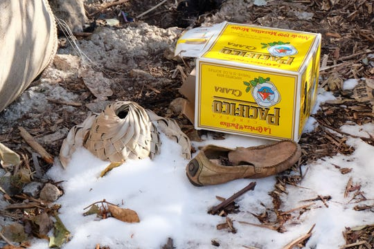 Outside an encampment under a footbridge, a straw hat, loafer and beer box sit in the snow on Friday, November 15, 2019 near Gilbert St.