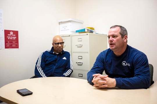 Perry Shawver, the co-owner of Quality Home Repair, talks with John Posey, a housing case manager at Shelter House, Thursday, Nov., 14, 2019, at Shelter House in Iowa City, Iowa.