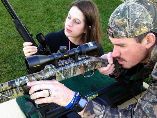 Ryan and Tristan Ellis of North Liberty have been a husband and wife deer hunting team for many years. Here she holds her Thompson muzzle-loader while he displays a Mossberg shotgun in a lead sled used to sight-in the guns.