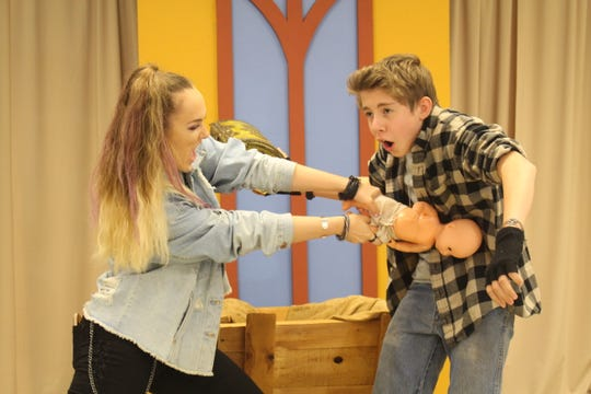 "Xandria Cross, left, as Imogene Herdman, and Remy Stavros, as Leroy Herdman, fight over the doll that represents baby Jesus in the WordPlayers' production of ""The Best Christmas Pageant Ever."""