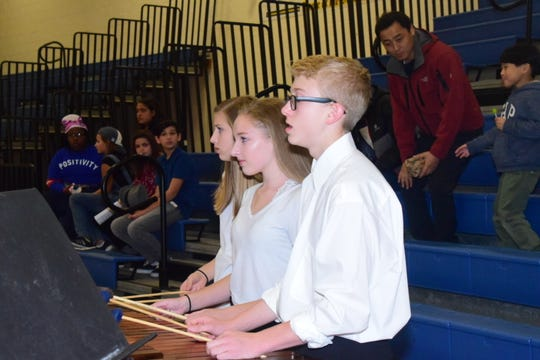 Marimba and xylophone players Sydney Huff, 14, Dustin Henderlight, 13, and Annamary Burkholder, 14, prepare to perform with the band at a Showcase held at Karns Middle School Tuesday, Nov. 12.