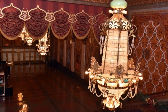 These 1928 Victor Pearl-built chandeliers hang in the lobby of the Tennessee Theatre. Burns and others worked to clean and restore them. Photos of the original building were used to re-create the draperies during the mid-2000s restoration.