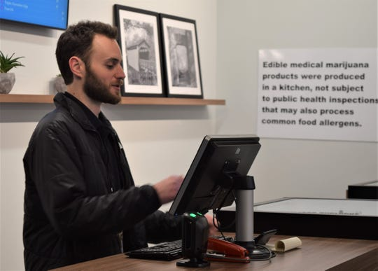 Chris Mastrilli, the general manager of Ohio Provisions by BCCO, checks the number of sales during a tour of the medical cannabis dispensary. Located in Carroll, the dispensary had a soft opening in September, but is now open for business.