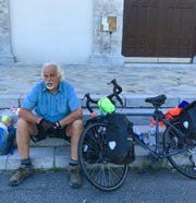Long distance bicyclist Bill Saint-Onge breaks for lunch on steps outside of a church in New Brunswick during his 2012 approximately 10,000-mile trek across eastern Canada. His next trip will take him around the globe.