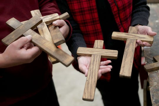 Dave Mack and Donna Bourget hold some of the 42 wooden crosses that Mack made in the workshop at his home in Waukesha.