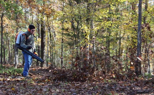 Lee Argyle of Lakeview blows leaves off the Dogwood Trail in Lakeview. The North Central Arkansas Master Naturalists' Trail Team cleared over 65 miles of trails last year.