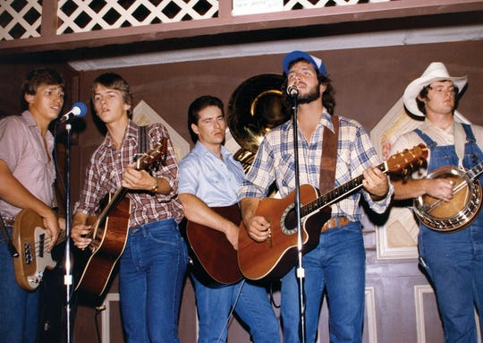 A young Garth Brooks and his band, including Ty England, left, perform in a  bar in the early days of his career.