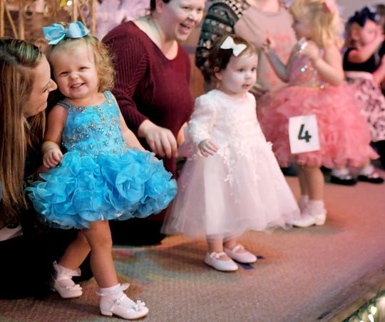 Heather Lewis presents her daughter, Blakely,1, on stage for the Miss Merry Christmas Beauty Pageant at the Stable Event Center in Centerville on Saturday, Nov, 7, 2019.