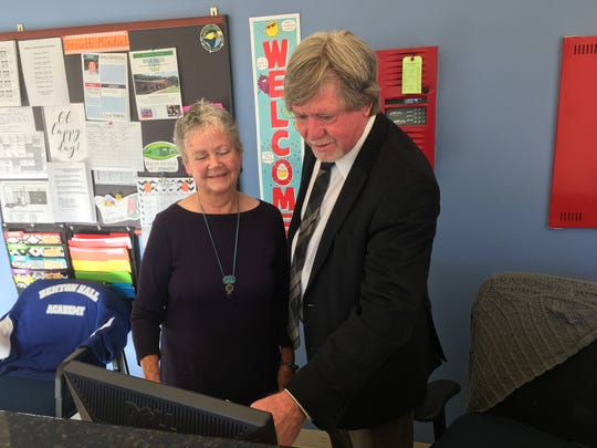 Benton Hall Academy board chair Jeannine Briley and head of school Jimmy Purcell check out a post online at the school's front desk.