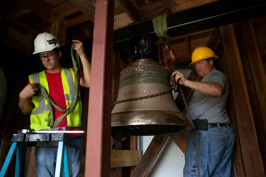 Verdin Company service technicians Taylor Hyer, left, and Ken Trolenberg install a bell, Wednesday, Nov. 13, 2019, inside the tower at Trinity by The Cove Episcopal Church in Naples