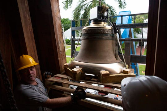 The Verdin Company service technicians, Ken Trolenberg, left, and Taylor Hyder guide in a 990-pound  bronze bell inside Trinity by The Cove Episcopal Church tower on Wednesday, Nov, 13, 2019, in Naples