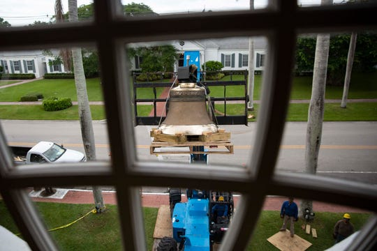 A lift operator slowly brings up the 990-pound bronze bell, Wednesday, Nov. 13, 2019, for installation inside Trinity by The Cove Episcopal Church tower in Naples.