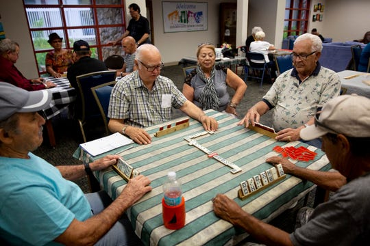From left to right, Manuel Vidal, Jorge Conrow, Korina Carraballo, Miguel Serrano, and Juan Betancurt play dominoes after a free hot lunch program at Golden Gate Senior Center on Friday, November 15, 2019.