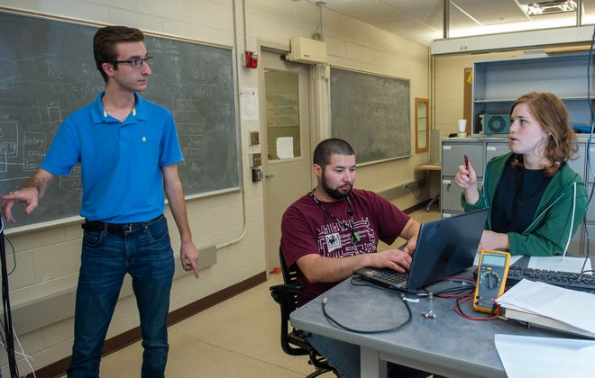 Esther Thompson and Dominick Gonzales, speak with Sean Tierney in a lab in the Physics building.
