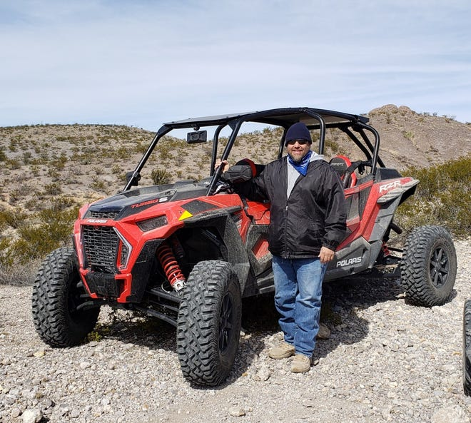 Daniel Alejo poses with his Polaris RZR 1000, his UTV, in the Doña Ana Mountains.