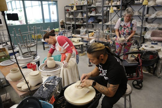 Kellie Bowers, left, Matt Bahe and Maryanne Greenwood work on pieces for the Charity Bowl Sale in the ceramics room at San Juan College on Nov. 14, 2019.