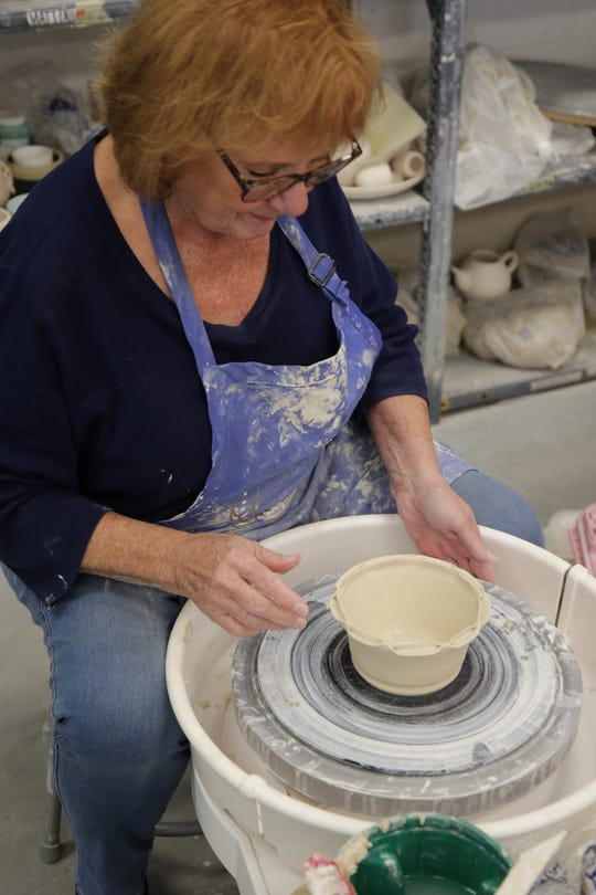 Cheryl Campbell fashions a rim on a piece for the San Juan College Charity Bowl Sale on Nov. 14, 2019.