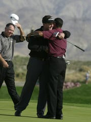 Phil Mickelson and Tiger Woods hug after the finish of the 2002 Skins Game as Mark O'Meara looks on at the Landmark Golf Club in Indio on Sunday.