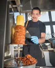 Cook Cesar Morales slices pork meat off the trompo, a vertical rotating spit, as he prepares tacos al pastor at La Parrilla restaurant on Nine Mile Road in Pensacola on Friday.