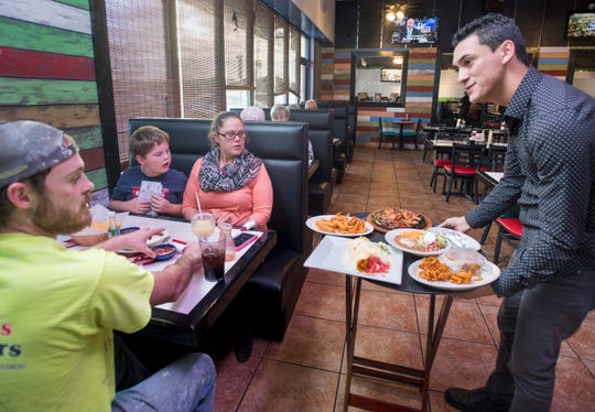 Manager Roberto Sarmiento, right, serves meals to the Douglas family at La Parrilla Grill on Friday.