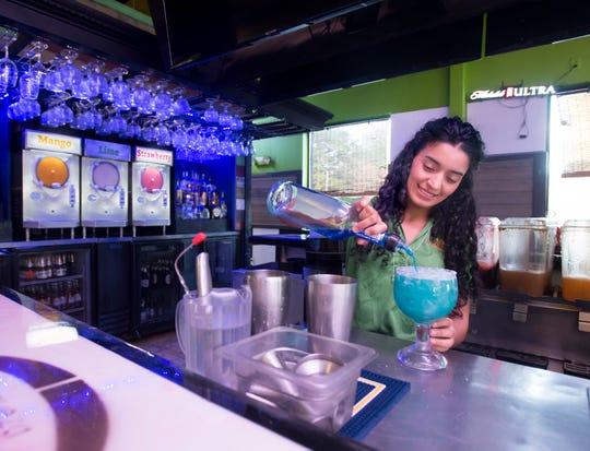 Rosa Sarmiento prepares a blue margarita at La Parrilla Grill in Pensacola.
