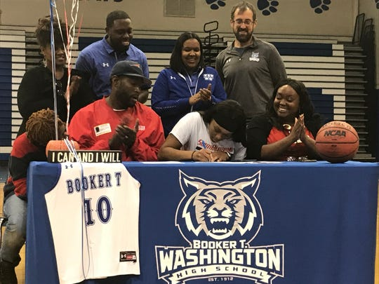 Booker T. Washington senior Janelle Jones (front, white shirt) signs a basketball scholarship with South Alabama on Friday, Nov. 15, 2019.