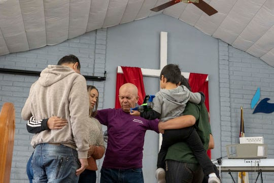 Asylum seekers Claudineia Ferreira Rodrigues Moraes, 40, and her husband Adriano moraes da Silva, 43, from Brazil (left) and Sandra Estefania Lema Guaraca, 20, with her 3-year-old son Derick from Ecuador, prays with Co-pastor Hector Ramirez after they were released by ICE at Iglesia Cristiana El Buen Pastor Church in Mesa, Arizona.