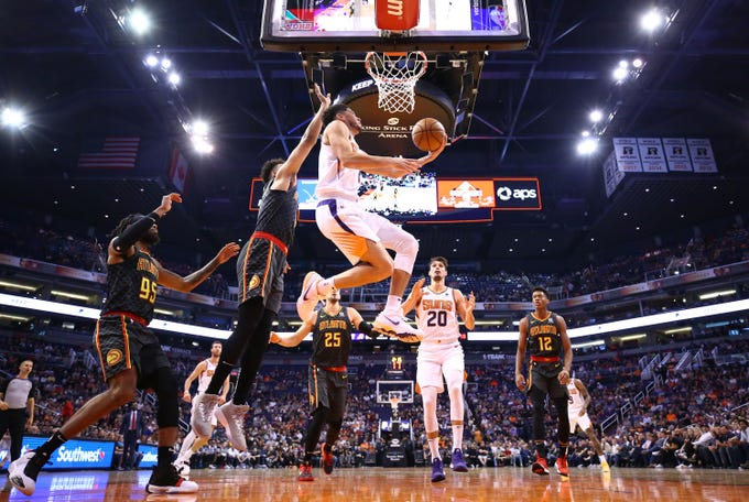 Phoenix Suns guard Devin Booker (1) makes a reverse lay-up against the Atlanta Hawks in the first half on Nov. 14, 2019 in Phoenix, Ariz.