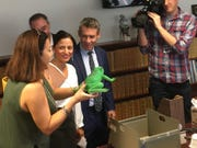 """Democrat lawmakers Isela Blanc of Tempe and Aaron Lieberman of Paradise Valley are joined by Phoenix resident Raquel Mamani on Nov. 15, 2019, in the House. They submitted the first bill in the chamber, placing the draft in a """"hopper"""" where a plastic frog serves as a paperweight. The bill would repeal protections for short-term rental properties."""