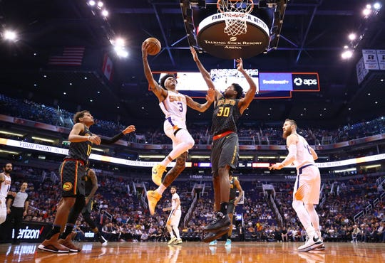 Phoenix Suns forward Kelly Oubre Jr. (3) drive to the basket and scores past Atlanta Hawks center Damian Jones (30) in the first half on Nov. 14, 2019 in Phoenix, Ariz.