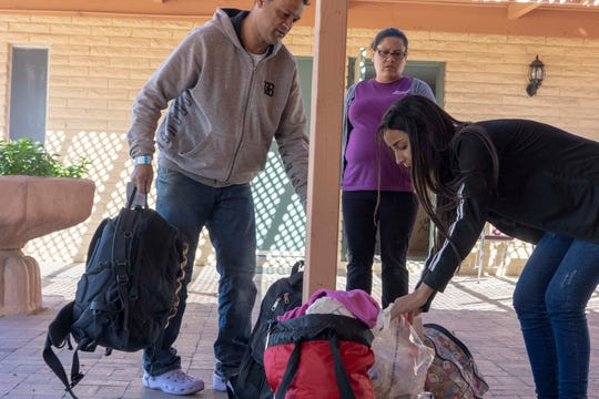 Volunteer members help Adriano Moraes da Silva, 43, and his daughter Rikelly Stephany Rodrigues Moraes, 16, get food and clothing after the asylum seekers from Brazil were released by ICE at Iglesia Cristiana El Buen Pastor Church in Mesa, Arizona.