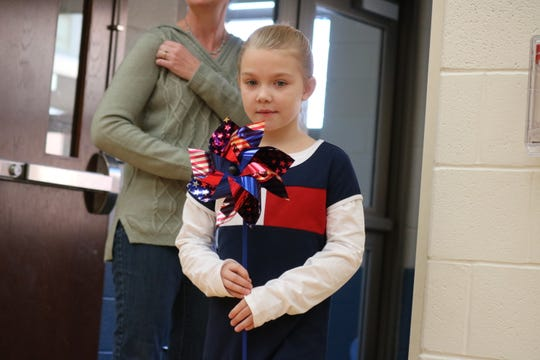 "Kambree Aiken, of Bataan Memorial School, presents a patriotic pinwheel as part of the annual ""Bataan Day"" assembly on Friday."