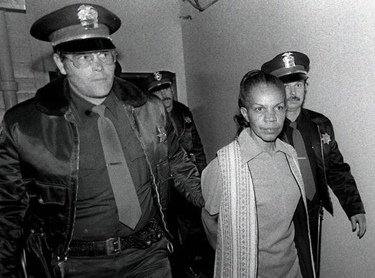 "Reno police escort Priscilla Ford into the police department following her arrest Thanksgiving Day in 1980. She was charged with murdering six people (another died later) and attempting to murder at 23 others. It was at this point she stopped in front of the photographer and said ""Oh my, you're a pretty one. I'll remember who you are."""