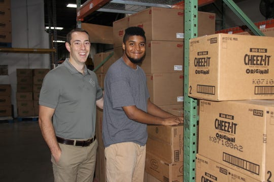 Mark Houseknecht, vice president of operations for Crickler Vending in Henrietta, with employee Kemori Spence, of Brighton. Spence was hired via an innovative, internship program with The ARC of Monroe.