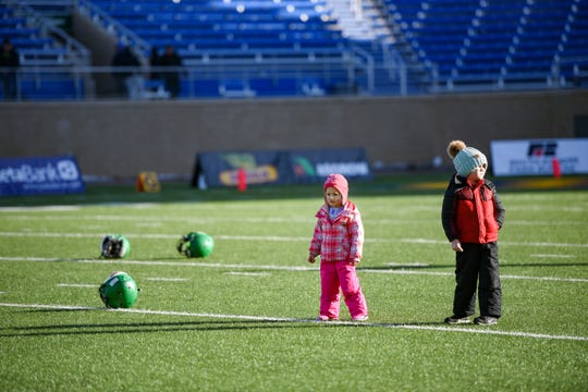 Two small children take the field after the Class 11AA state football finals on Friday, Nov. 15, at the Dana J. Dykehouse Stadium in Brookings.
