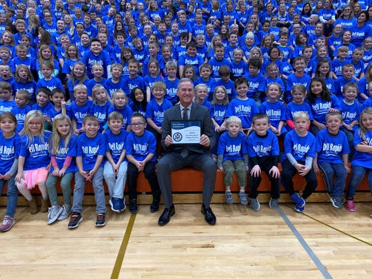 Former Governor Dennis Daugaard poses with students from Dells Elementary on Friday, Nov. 15 in observance of winning the Blue Ribbon Award from the U.S. Department of Education.