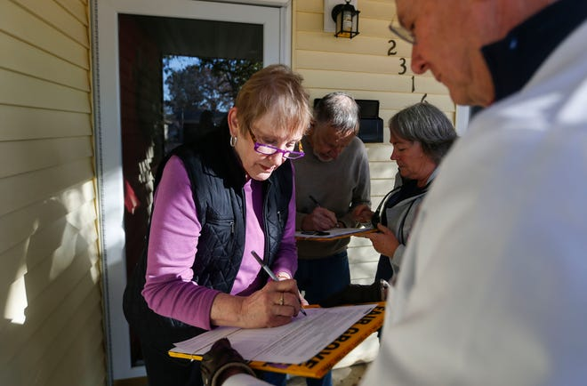 Janice and Fred Bausman sign a petition with Dr. Doug McNeal and RN Susie Strozewski to expand Medicaid in Missouri on Friday, Nov. 15, 2019.