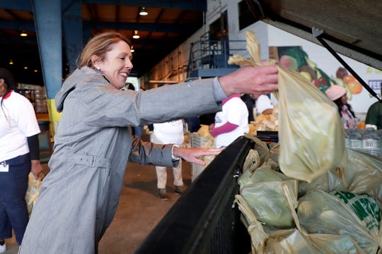 Sherri Hall places bags of food in a truck as she volunteers for the Farm Share holiday food distribution day on Friday, Nov. 15, 2019.