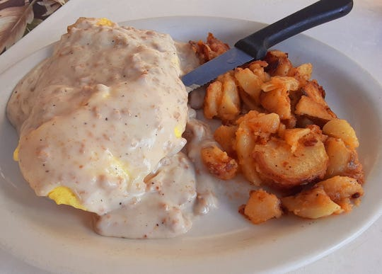 The Country Scrambled platter at Alice's Family Restaurant offers a bounty of scrambled eggs, sausage patties and biscuits smothered in country sausage gravy and served with your choice of an accompaniment. The side here is home fries with sauteed onions.