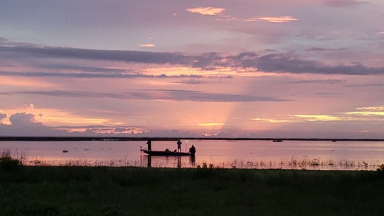 The rays of the sun crack through the clouds on the horizon Friday morning at Lock 7 along Lake Okeechobee's north shore.